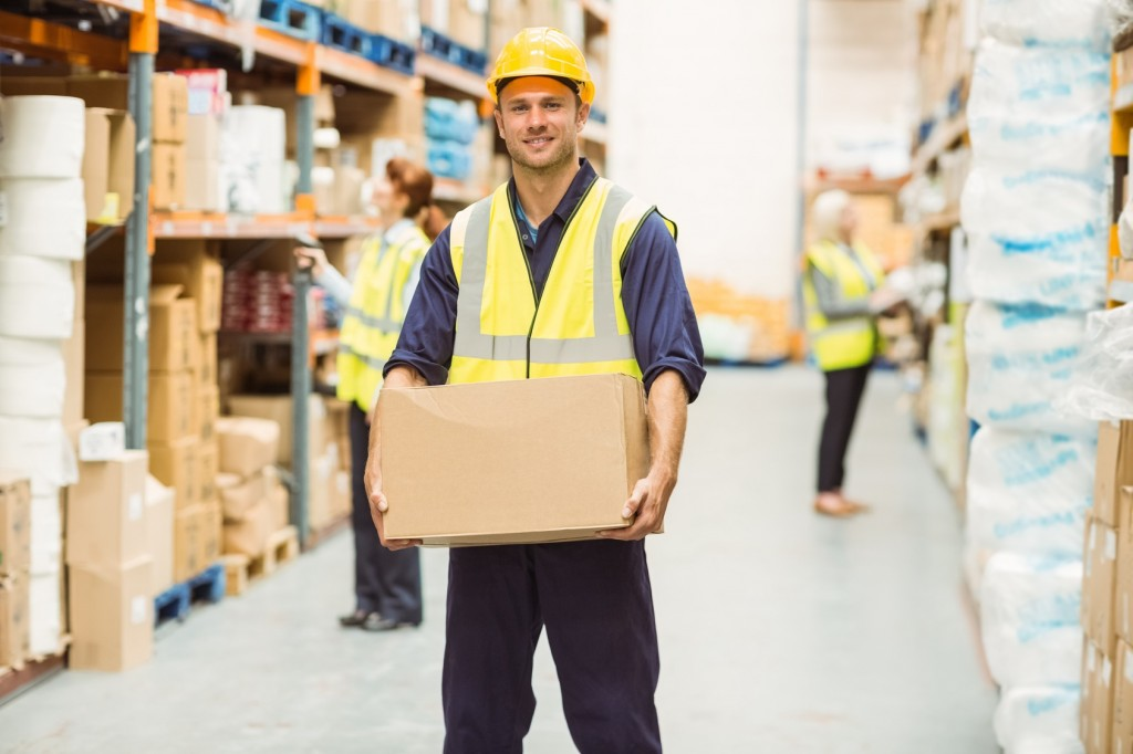 Warehouse worker smiling at camera carrying a box