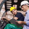 Warehouse manager talking with forklift driver in warehouse